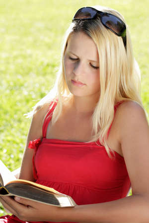 young, blond girl reading a book, summertime in the countryside photo