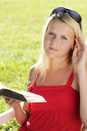 blond teenage girl with a book, sunny outdoor shot photo