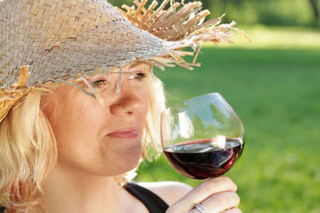 Woman with straw hat smelling and tasting red wine in the countryside photo