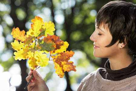 Woman with autumn leaves, sunny autumn outdoor shot photo