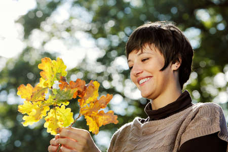 Autumn - pretty young woman looking at a branch with autumn leaves photo