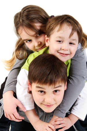 Three funny siblings, girl and boys on top of each other. photo