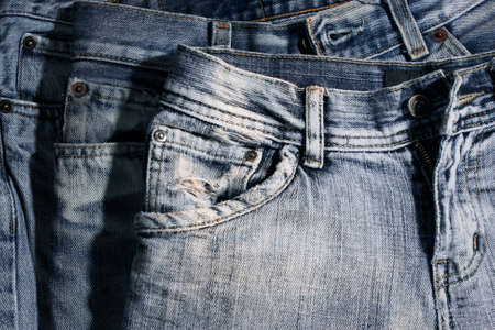 denim background: Worn and washed out jeans, front side. Stock Photo