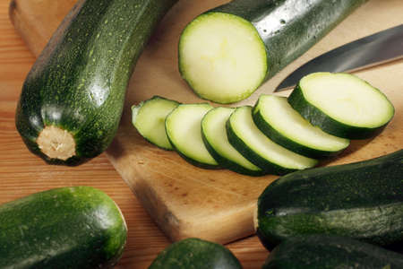 Fresh, ripe and green zucchini, sliced, on a wooden background. Stock Photo