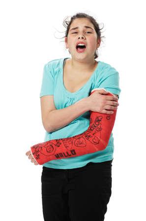 fractura: Ni�a con yeso rojo tiene dolor y sostiene su brazo roto Foto de archivo