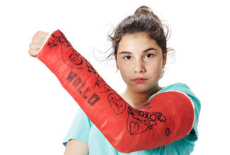 Sad looking girl with red plaster cast photo