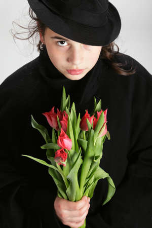 Sad looking teenage girl with tulips photo