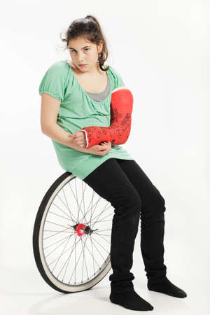 Girl with wheel and plaster cast. Studio shot against a white background.