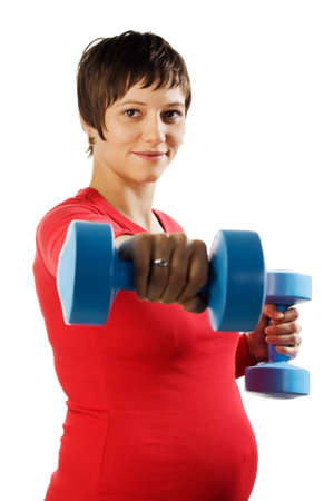 Young pregnant woman in a red shirt making fitness exercises. Stock Photo