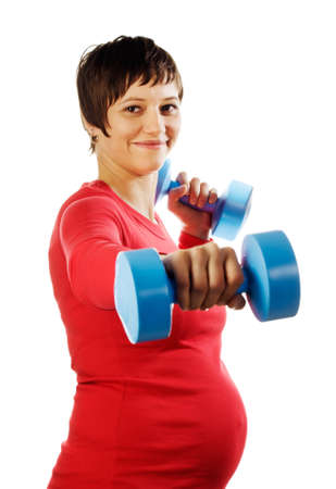 Young pregnant woman in a red shirt with dumbbells.