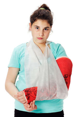 Girl with red plaster cast and sling looking sadly. photo