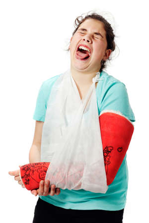 Girl with red cast and sling bandage has pain and holds her broken arm. Stock Photo