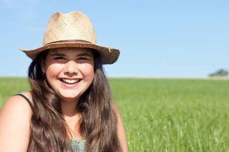 sunhat: Happy girl with sun hat. Outdoor shot against a blue sky.