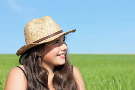 Laughing girl with sun hat. Outdoor shot against a blue sky. Stock Photo
