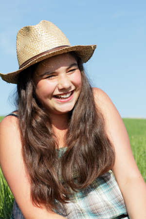 Laughing girl with sun hat. Outdoor shot against a blue sky. Stock Photo - 10023063