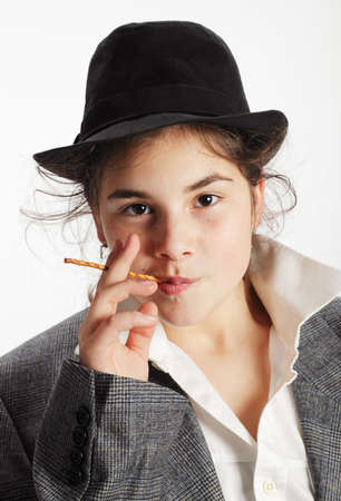 pretzel stick: Teenage girl with black hat and suit, holding a pretzel stick to her mouth. Stock Photo