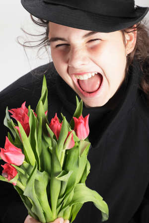 fooling: Teenage girl with a bouquet of tulips makes silly faces and fooling around.