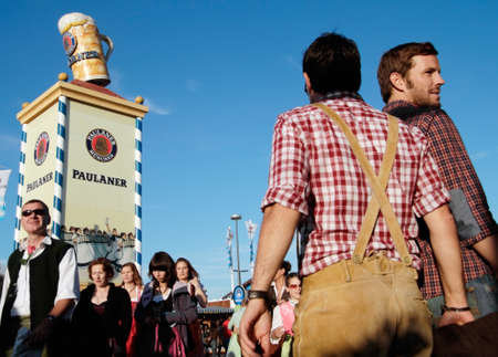 Munich, Germany - October 03, 2010: In the foreground two men in bavarian costume at the traditional Oktoberfest at the Theresienwiese, in the background a tower of the Bavarian beer brand Paulaner for advertising.