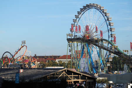Munich, Germany - October 03, 2010: Panorama with Ferris Wheel next to a roller coaster at the traditional Oktoberfest at the Theresienwiese. Editorial