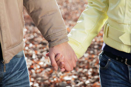 Couple in love holding hands together, autumn outdoor detail. photo