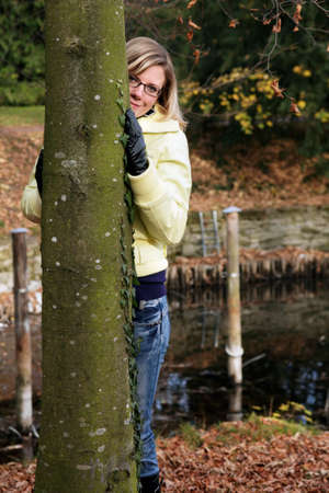 Hide and seek - autumn outdoor portrait of a pretty woman. photo