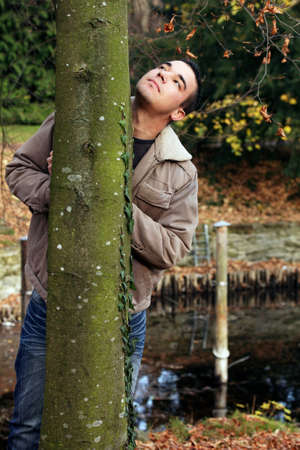 Autumnal outdoor shot of a young man behind a tree.