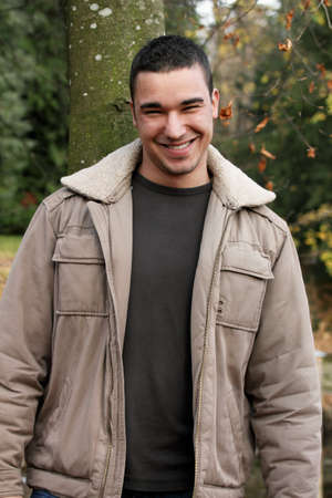 likable: Autumnal portrait of a handsome young man friendly smiling.