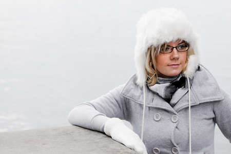 Pretty woman in warm winter outfit and a white wool cap. Stock Photo - 10837133