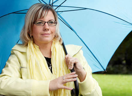 Young blond woman with blue umbrella and yellow jacket Stock Photo - 10956987