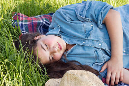 warm shirt: Young girl sleeping in the lawn. Summer outdoor shot. Stock Photo