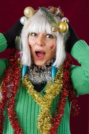 Christmas Surprise - festive decorated woman. Studio shot against a red background. photo