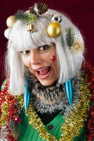 Crazy Christmas decorated woman. Festive decorated woman with open mouth. photo