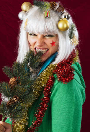 Bad Christmas woman. Woman in Christmas decoration biting into a branch.