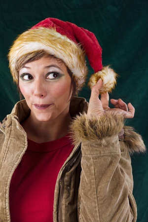 Cheeky female Santa Claus. Studio shot against a dark green background. photo