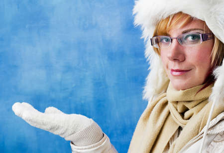 Pretty woman in winter clothing holding up her open hand palm, studio shot with copy space. photo