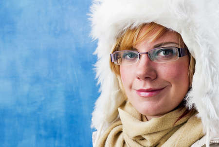 Charming young woman in winter clothes with white fur hat and scarf. photo