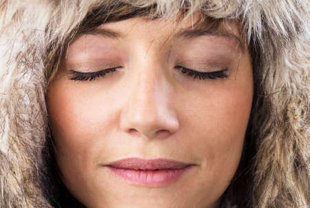Close-up portrait of beautiful caucasian young woman with closed eyes and fur hat. Stock Photo - 12025388
