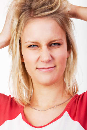 Young blonde woman tearing her hair and looks stressed. photo