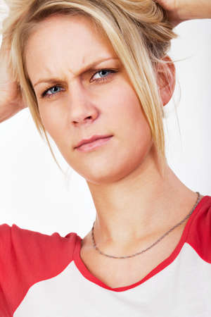 brows: Young blonde woman wrinkling her brow thoughtfully, Portrait. Stock Photo