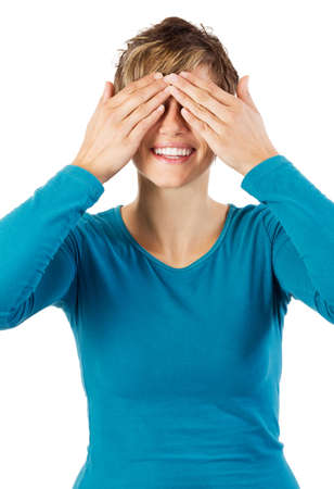 Smiling young woman covering her eyes with her hands  Stock Photo