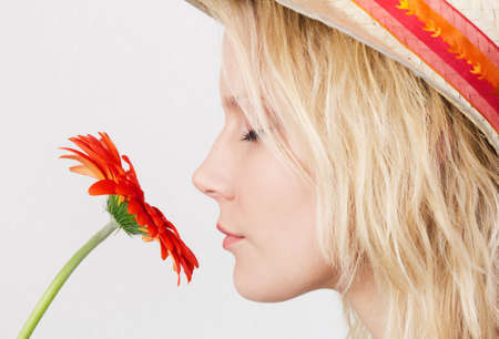 Portrait in profile of a pretty blonde woman with closed eyes smelling a red flower