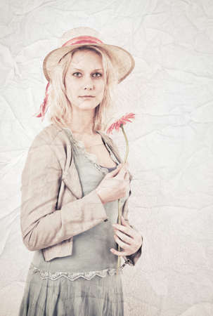 Vintage portrait of a blonde woman holding a flower  Yellowed photo with textured paper background  photo