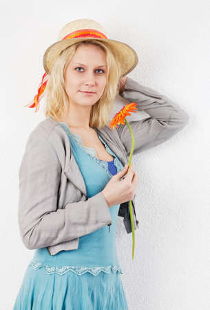 Summer portrait of a smiling blond woman with sun hat, holding a red gerbera  photo