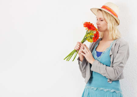 sun hat: Blond pretty woman with sun hat smelling a bouquet of flowers