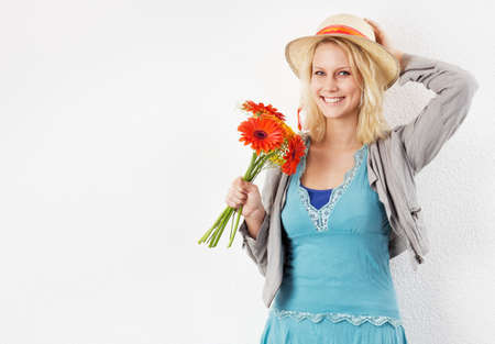 Smiling young blonde woman with sun hat and bouquet of flowers