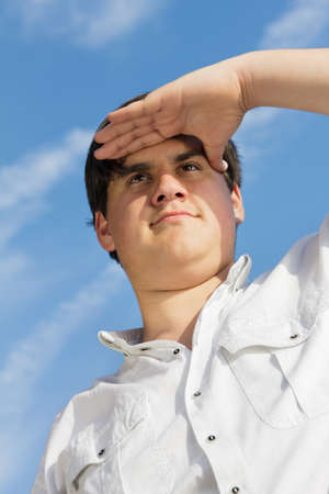 Teenage boy holding his hand on his forehead and looking into the distance  photo