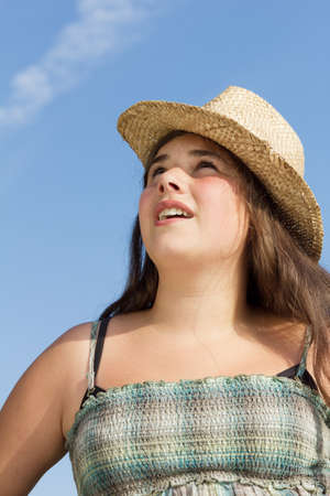 sun hat: Summer Portrait of a pretty girl with sun hat, looking up, outdoor shot against a blue sky