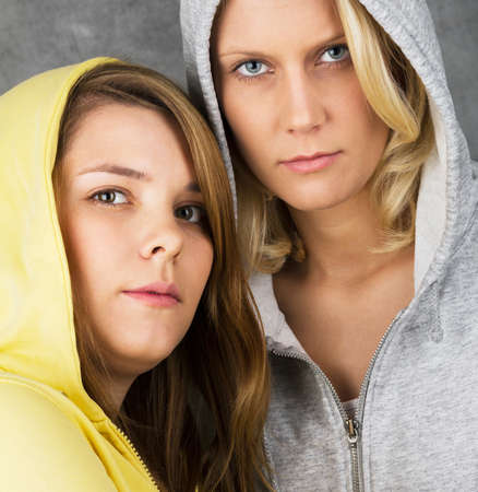 tough girl: Close up portrait of two teen girls seriously into the camera looking Stock Photo