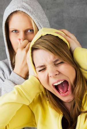 Two teenage girls, one is holding her nose, the other screams and holding her ears photo