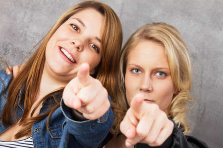 Portrait of two young women pointing with their fingers at the camera photo